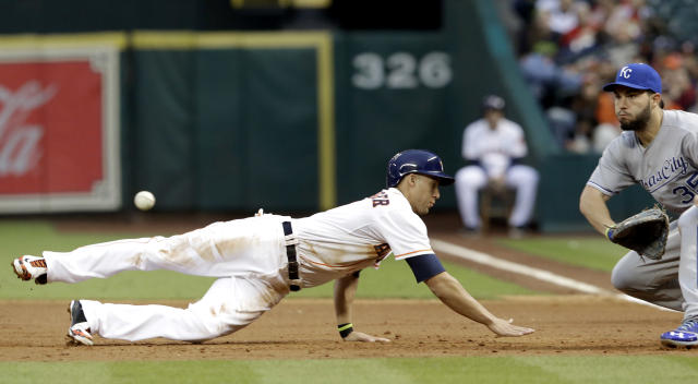 Houston Astros' George Springer, left, dives back to first base ahead of the ball as Kansas City Royals first baseman Eric Hosmer (35) waits for the throw in the first inning of a baseball game on Thursday, April 17, 2014, in Houston. (AP Photo/Pat Sullivan)