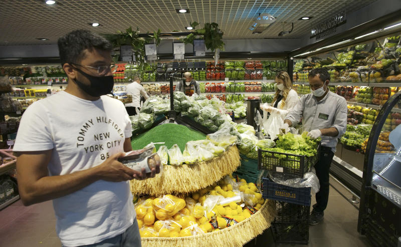 People wearing face masks for protection against the coronavirus, shop for food at a market hours before a four-day new curfew declared by the government in an attempt to control the spread of coronavirus, in Ankara, Turkey on May 22. (Burhan Ozbilici/AP Photo)
