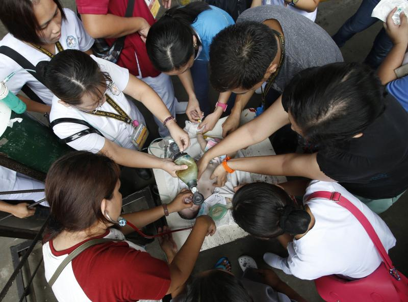 Medical workers work to revive newly-born baby at covered court in Cebu City