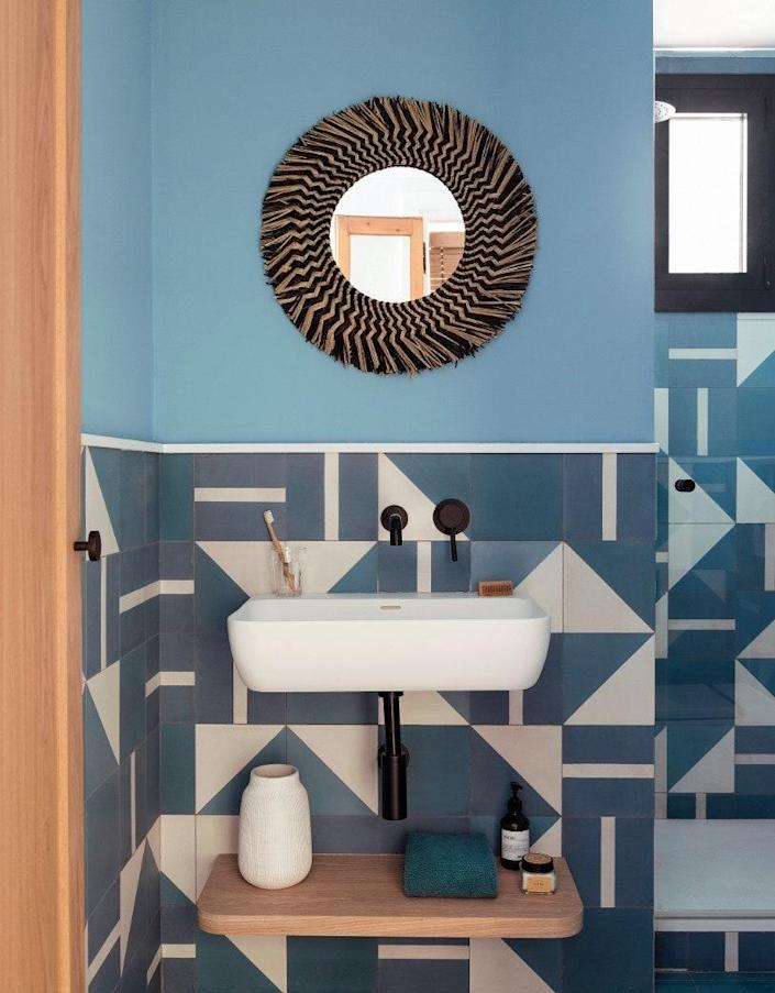 In the blue bathroom, the geometric tiles were made to measure and contrast with the curved mirror by Kave Home.