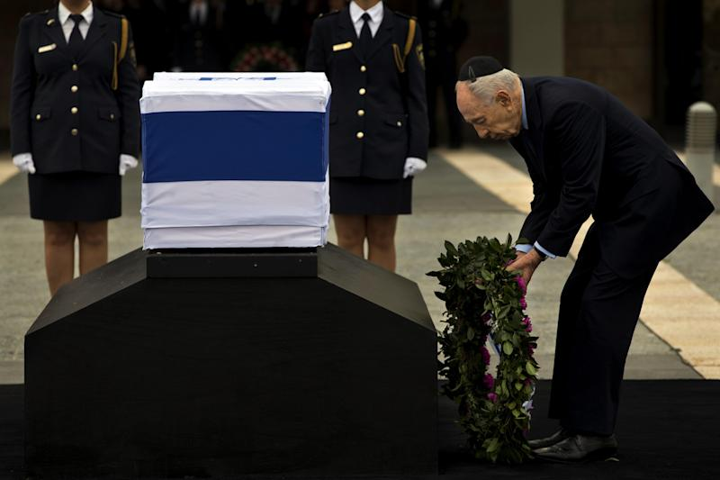 Israel's President Shimon Peres lays a wreath next the coffin of late Israeli Prime Minister Ariel Sharon at the Knesset Plaza, Israeli Parliament, in Jerusalem, Sunday, Jan. 12, 2014. Sharon, the hard-charging Israeli general and prime minister who was admired and hated for his battlefield exploits and ambitions to reshape the Middle East, died Saturday, eight years after a stroke left him in a coma from which he never awoke. He was 85. (AP Photo/Bernat Armangue)