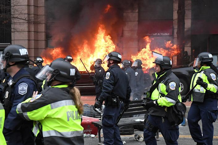 Police officers move protestors away from a car that was set on fire during protests near the inauguration of President Donald Trump in Washington, DC, U.S., January 20, 2017.