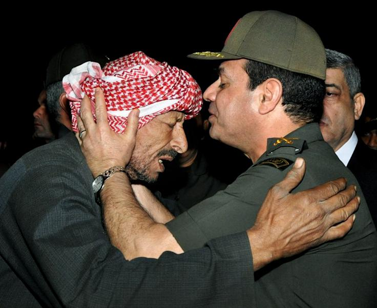 FILE - In this Nov. 20, 2013, file photo released on the official Facebook page of the Egyptian Military spokesman of the Armed Forces, Egyptian Defense Minister Gen. Abdel-Fattah el-Sissi, right, kisses the forehead of a relative of a 2nd Field Army solider who was killed after a suicide bomber rammed his explosive-laden car into one of two buses carrying off-duty soldiers, at the road between the border town of Rafah and the coastal city of el-Arish, during their funeral procession in Cairo. The head of Egypt's military, Abdel-Fattah el-Sissi, is riding on a wave of popular fervor that is almost certain to carry him to election as president. Unknown only two years ago, a broad sector of Egyptians now hail him as the nation's savior after he ousted the Islamists from power, and the state-backed personality cult around him is so eclipsing, it may be difficult to find a candidate to oppose him if he runs. Still, if he becomes president, he faces the tough job of ruling a deeply divided nation that has already turned against two leaders.(AP Photo/The Official Facebook Page of the Egyptian Military spokesman of the Armed Forces, File)