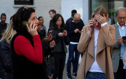 People react near Parsons Green tube station - Credit: HANNAH MCKAY/Reuters