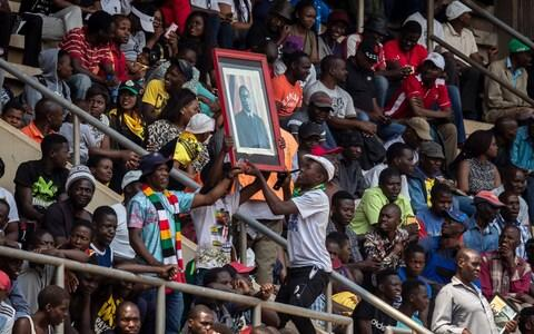 Mourners hold a portrait of Robert Mugabe - Credit: Ben Curtis/AP