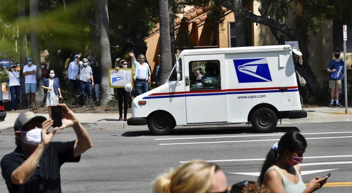 A postal carrier drives past protesters during a rally against changes to the United States Postal Service, in Newport Beach, Calif., Tuesday, Aug., 18, 2020. Facing mounting public pressure and a crush of state lawsuits, President Donald Trump's new postmaster general announced Tuesday he is halting some operational changes to mail delivery that critics blamed for widespread delays and warned could disrupt the November election.(Jeff Gritchen/The Orange County Register via AP)