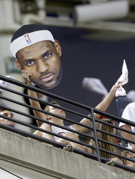 A fan holds up a poster of LeBron James poster at the Cleveland Indians vs New York Yankees baseball game Thursday, July 10, 2014, in Cleveland. (AP Photo/Tony Dejak)