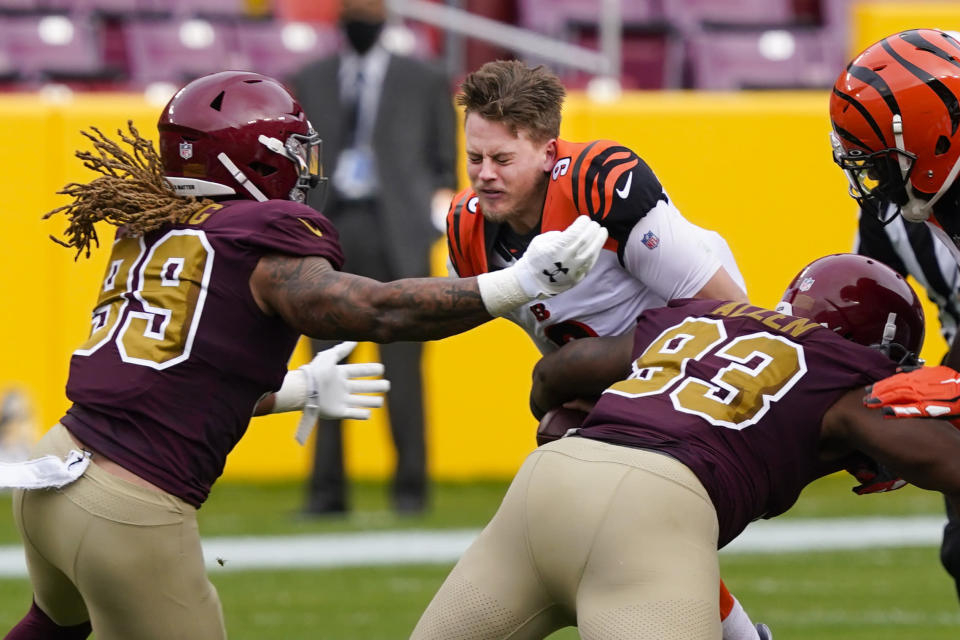 Cincinnati Bengals quarterback Joe Burrow (9) looses his helmet as he is tackled by Washington Football Team defensive tackle Jonathan Allen (93) and defensive end Chase Young (99), during the first half of an NFL football game, Sunday, Nov. 22, 2020, in Landover. (AP Photo/Susan Walsh)