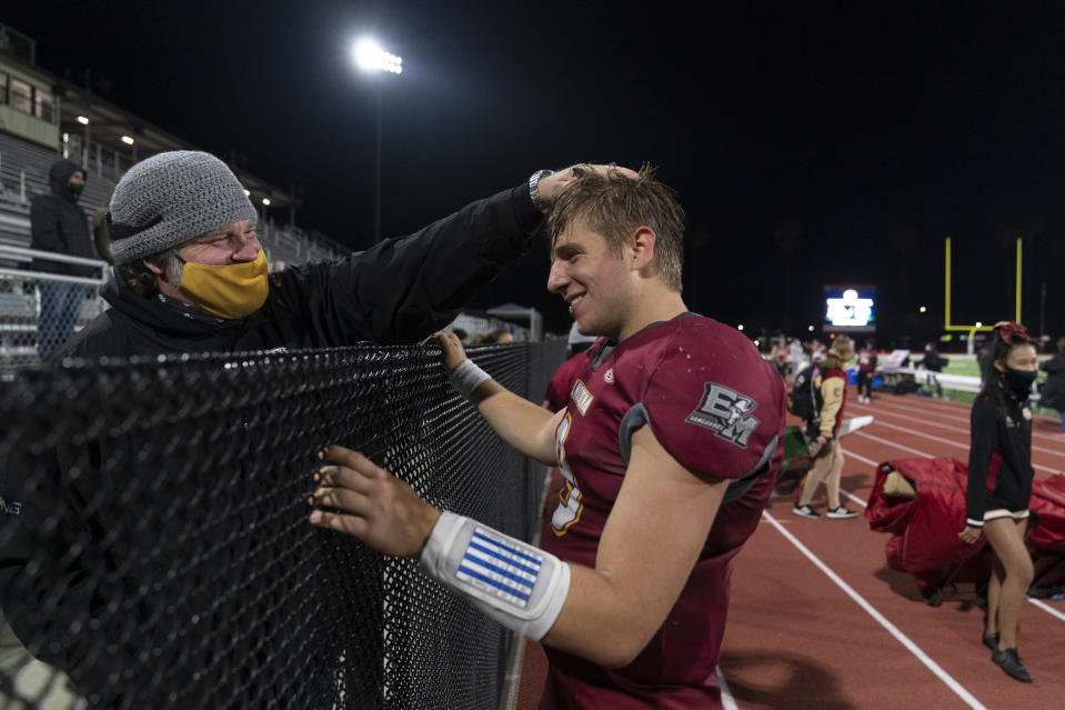 """El Modena quarterback Jackson Keays, right, is congratulated by his father, Joe, after the team's 42-20 win against El Dorado in a high school football game in Orange, Calif., Friday, March 19, 2021. """"We had to keep staying positive and keep believing there is going to be an opportunity to have a football season,"""" said the father. """"Thank God it came through."""" (AP Photo/Jae C. Hong)"""