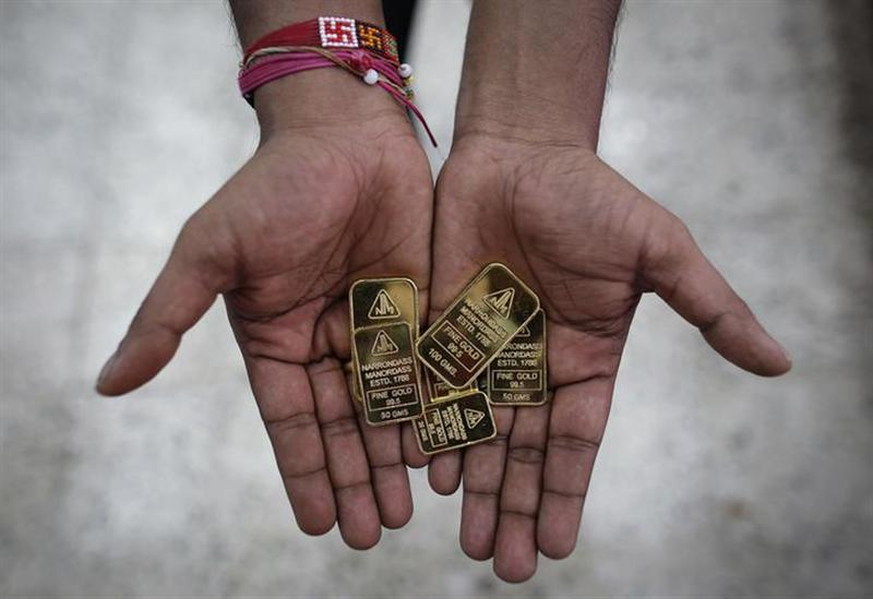 An employee poses with gold biscuits inside a jewellery showroom in Mumbai June 4, 2013.