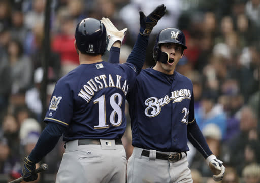 Milwaukee Brewers' Mike Moustakas, left, congratulates Christian Yelich after Yelich scored on a ground ball hit by Travis Shaw against the Colorado Rockies in the first inning of Game 3 of a baseball National League Division Series, Sunday, Oct. 7, 2018, in Denver. (AP Photo/Joe Mahoney)