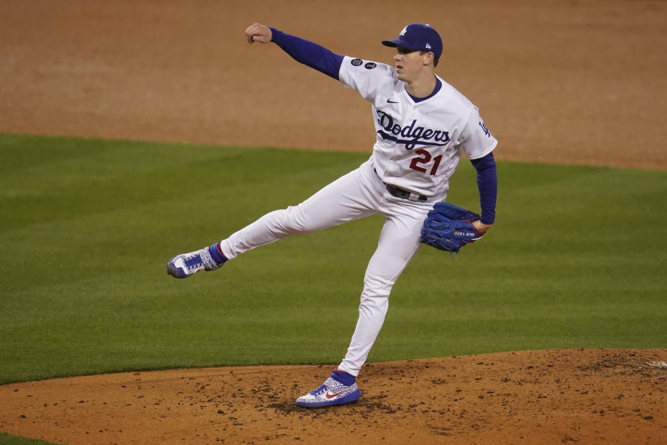 Los Angeles Dodgers starting pitcher Walker Buehler watches a throw to a San Diego Padres batter during the third inning of a baseball game Thursday, April 22, 2021, in Los Angeles. (AP Photo/Marcio Jose Sanchez)