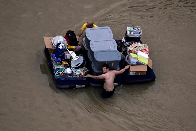<p>Residents wade with their belongings through flood waters brought by Tropical Storm Harvey in Northwest Houston, Texas, Aug. 30, 2017. (Photo: Adrees Latif/Reuters) </p>