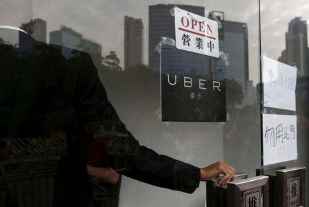 An open sign is seen at the office of taxi-hailing service Uber Inc during a driver recruitment event in Hong Kong, China December 29, 2015. REUTERS/Tyrone Siu/Files