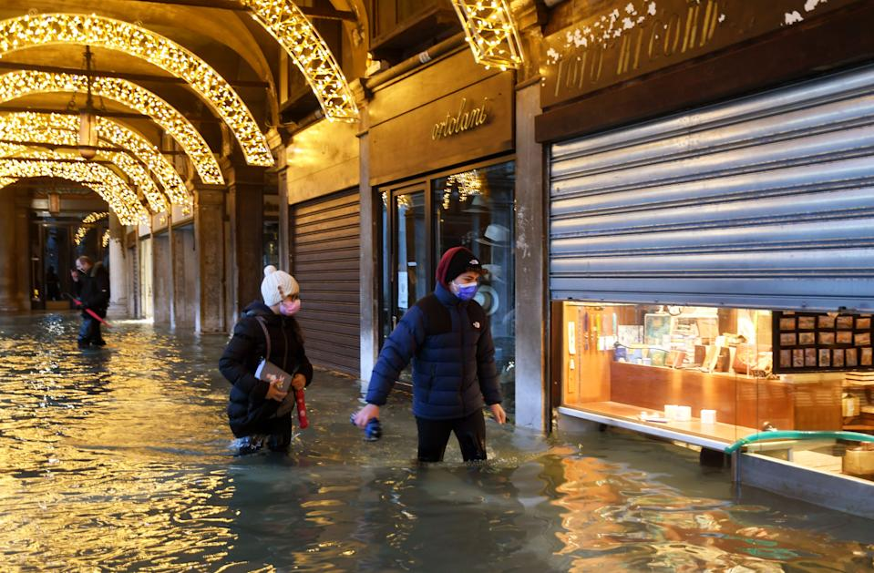 "People walk across an shopping arcade by a flooded St. Mark's Square on December 8, 2020 in Venice following a high tide ""Alta Acqua"" event following heavy rains and strong winds, and the mobile gates of the MOSE Experimental Electromechanical Module that protects the city of Venice from floods, were not lifted (Photo by ANDREA PATTARO / AFP) (Photo by ANDREA PATTARO/AFP via Getty Images)"