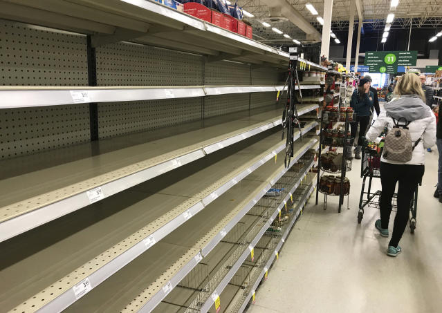 Shoppers walk by near empty shelves at a grocery store in North Vancouver, British Columbia, Saturday, March 14, 2020. (Jonathan Hayward/The Canadian Press via AP)