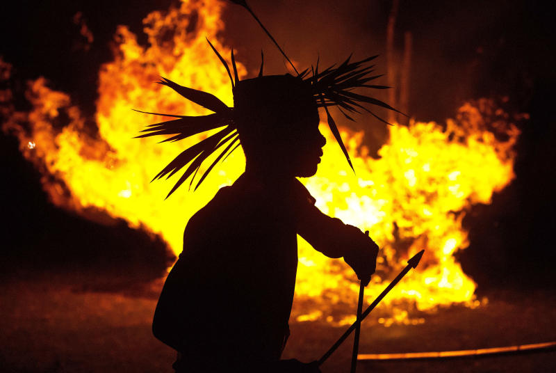 In this Monday, June 10, 2019 photo, an Indian Rabha tribal Hindu priest dances around burning charcoal as part of rituals during Baikho festival at Pantan village, west of Gauhati, India. Every year, the community in India's northeastern state of Assam celebrates the festival, to please a deity of wealth and ask for good rains and a good harvest. (AP Photo/Anupam Nath)