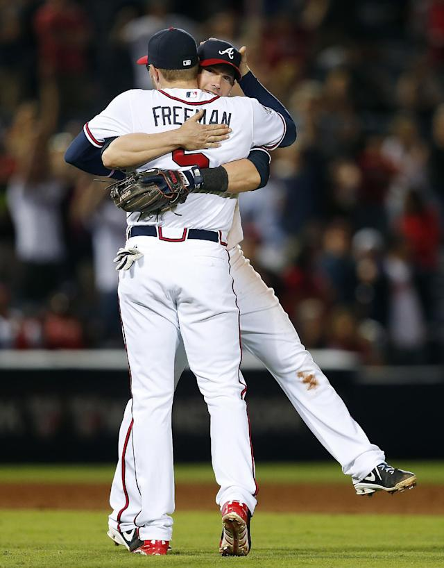 Atlanta Braves third baseman Chris Johnson (23) and Atlanta Braves first baseman Freddie Freeman (5) embrace after defeating Cincinnati Reds 5-4 in a baseball game Friday, April , 25, 2014 in Atlanta. (AP Photo/John Bazemore)