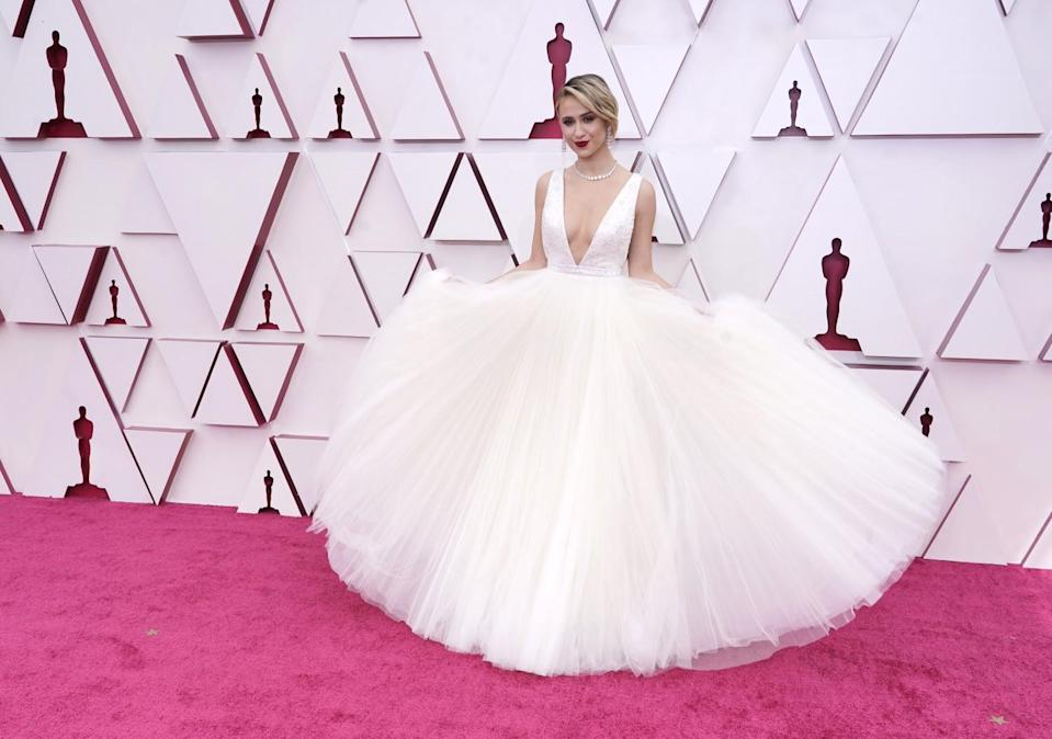 Maria Bakalova in a white dress with a voluminous tulle skirt and a plunging neckline.
