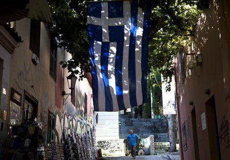 A souvenir shop owner cleans the sidewalk at the Plaka district under the Acropolis hill in Athens