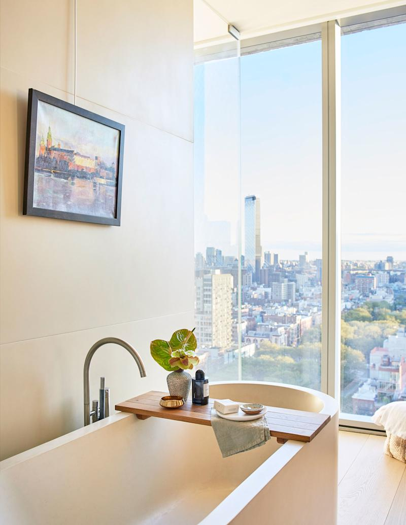 """In the master bath, the deep tub is decorated with accessories from Côte à Coast and Homenature in New York. Above it hangs a landscape painting from Ostrego's birthplace, Krakow, purchased by his father at Florian's Gate. """"It's a reminder of the sacrifices my parents made to be here in the U.S.,"""" he says."""