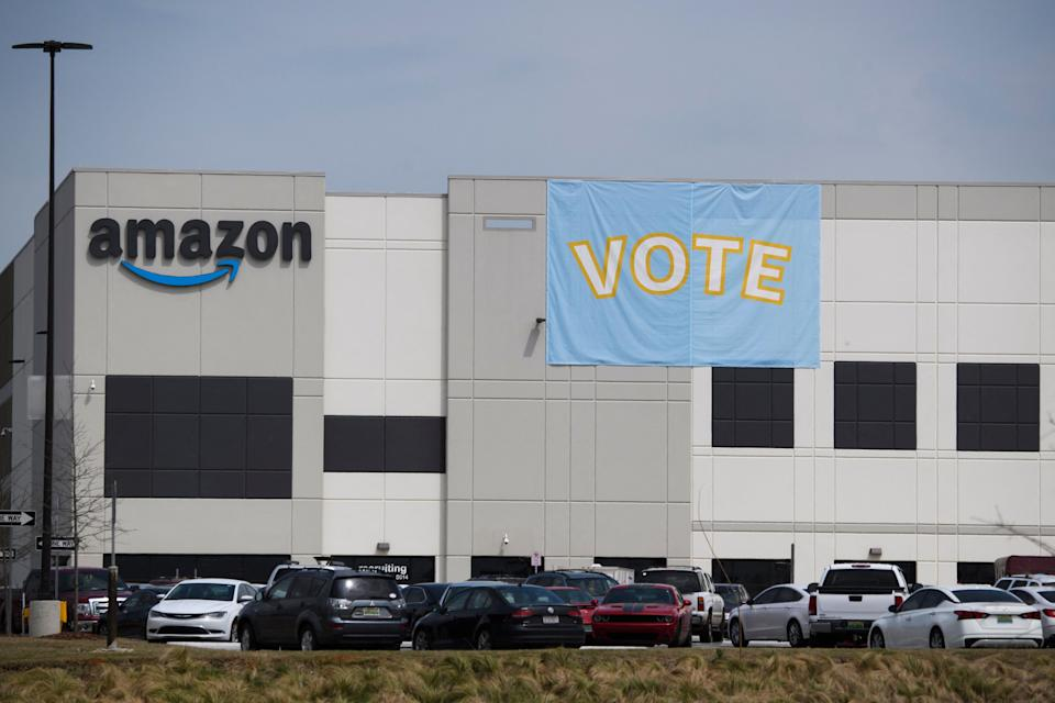 Vote signage hangs outside the Amazon.com, Inc. fulfillment center in Bessemer, Alabama on March 26, 2021. - Senator Bernie Sanders joined the drive March 26, 2021, to unionize Amazon workers in Alabama with the Retail, Wholesale and Department Store Union (RWDSU) in Birmingham, as clashes intensified between lawmakers and the e-commerce giant ahead of a deadline for a vote that could lead to the first union on US soil at the massive tech company. The visit marks the latest high-profile appearance in the contentious organizing effort for some 5,800 employees at Amazon's warehouse in Bessemer which culminates next week. (Photo by Patrick T. FALLON / AFP) (Photo by PATRICK T. FALLON/AFP via Getty Images)