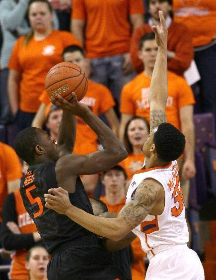 Miami's Davon Reed, left, shoots near Clemson's K.J. McDaniels during the first half at of an NCAA college basketball game at Littlejohn Coliseum Tuesday, March 4, 2014, in Clemson, S.C.. (AP PHOTO/Ken Ruinard/ Anderson Independent Mail)