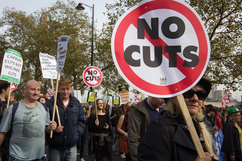 """London, England - October 20, 2012: Protesters march against David Cameron's Coalition Government spending cuts that are taking place in the UK public sector. In the image, a woman is brandishing a placard reading 'No Cuts'"""