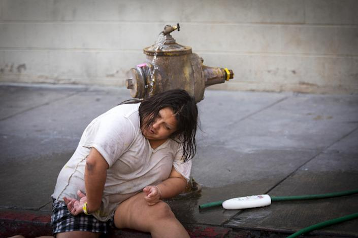 """Monica Ruiz, 32, cools down in the water from a fire hydrant on Crocker Street in downtown L.A. on Sept. 6. <span class=""""copyright"""">(Francine Orr / Los Angeles Times)</span>"""