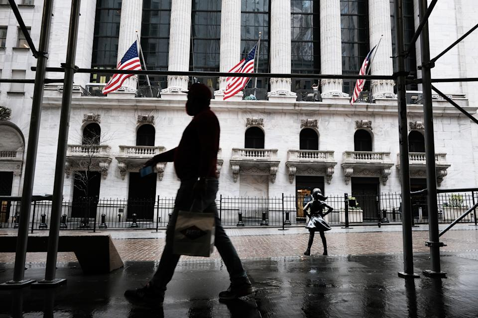 NEW YORK, NY - APRIL 15: People pass the New York Stock Exchange on April 15, 2021 in New York.  After large companies reported strong profits and new economic data point to a recovery in consumer spending, US stocks rose to record levels on Thursday.  (Photo by Spencer Platt / Getty Images)