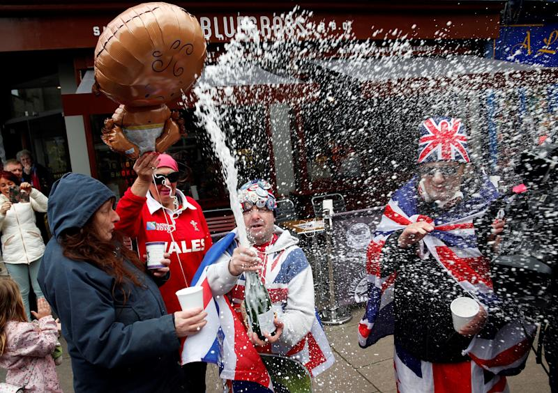 Royal super fans John Loughery (C) pops the cork on a bottle of Champagne, as they stand near Windsor Castle on Monday, following the announcement that Meghan, Duchess of Sussex, has given birth to a son. (Photo: ADRIAN DENNIS via Getty Images)