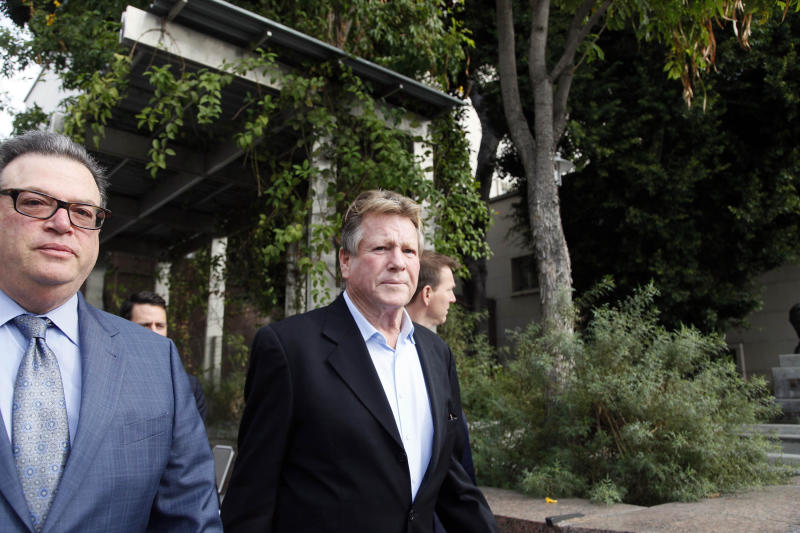 In this Monday, Dec. 2, 2013 file photo, actor Ryan O'Neal, right, leaves court after he testified in a Los Angeles courtroom about his relationship with Farrah Fawcett and his claimed ownership of an Andy Warhol portrait of the actress. A judge ruled Thursday, Dec. 5, 2013, that a former caregiver for Fawcett can testify about a conversation in which she says the actress told her that a Warhol portrait that is at the center of the ownership dispute belonged to O'Neal. The actor is seeking to keep the artwork while Fawcett's alma mater the University of Texas at Austin is suing to obtain the 1980 portrait. (AP Photo/Nick Ut, File)