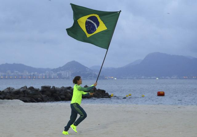 2016 Rio Olympics - Sailing - Victory Ceremony - Women's Skiff - 49er FX - Victory Ceremony - Marina de Gloria - Rio de Janeiro, Brazil - 18/08/2016. Martine Grael (BRA) of Brazil runs holding Brazil's flag. REUTERS/Brian Snyder FOR EDITORIAL USE ONLY. NOT FOR SALE FOR MARKETING OR ADVERTISING CAMPAIGNS.