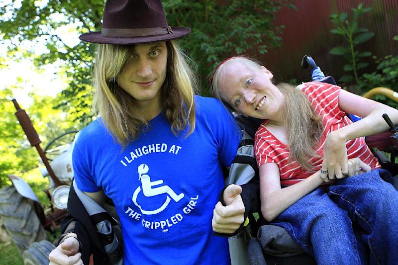 "Ally Bruener, right, poses for a photograph with friend Forest Thomer at her Alexandria, Ky. home on June 13, 2012. Thomer,  who says he was charged with disorderly conduct after using the word ""crippled"" to promote a comedian with muscular dystrophy claims Cincinnati police violated his free speech rights, and the comedian agrees. Thomer, of Cold Spring, Ky., is to appear in a Cincinnati courtroom on the charge Wednesday. He was cited by Cincinnati police last month at a park after he and Bruener say he asked people if they wanted to ""laugh at the crippled girl.""  (AP Photo/The Cincinnati Enquirer, Cara Owsley)  MANDATORY CREDIT;"