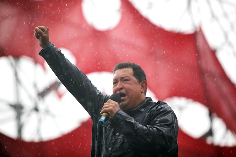 Under a pouring rain Venezuela's President Hugo Chavez delivers a speech to supporters during his closing campaign rally in Caracas, Venezuela, Thursday, Oct. 4, 2012. Chavez is running for re-election against opposition candidate Henrique Capriles on Oct. 7. (AP Photo/Rodrigo Abd)