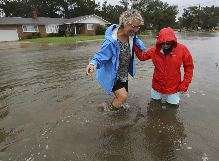 St. Mary's: Anne Herring (right) helps support her friend Jen Fabrick (left) as they walk through flood waters near their homes on St. Mary's Street while Hurricane Dorian passes by on Sept. 4, 2019, at St. Mary's. (Photo: Curtis Compton/Atlanta Journal-Constitution via AP)
