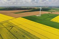 FILE PHOTO: Aerial view shows power-generating windmill turbine amidst rapeseed fields, in Saint-Hilaire-lez-Cambrai