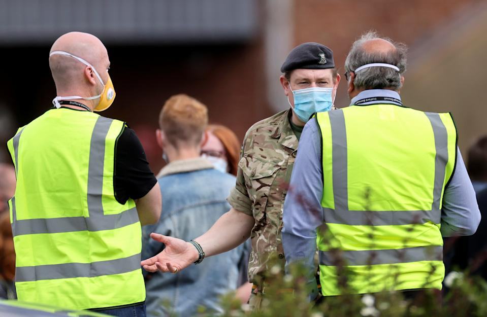 A soldier wearing a face mask gestures as people queue near the Crown and Anchor pub following a spike in cases of the coronavirus disease (COVID-19) to visitors of the pub in Stone, Britain, July 29, 2020. REUTERS/Carl Recine