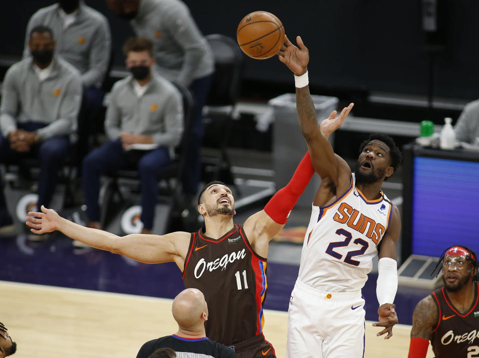 Phoenix Suns' Deandre Ayton wins the tip-off against the Portland Trail Blazers' Enes Kanter during the first half of an NBA basketball game Monday, Feb. 22, 2021, in Phoenix. (AP Photo/Darryl Webb)
