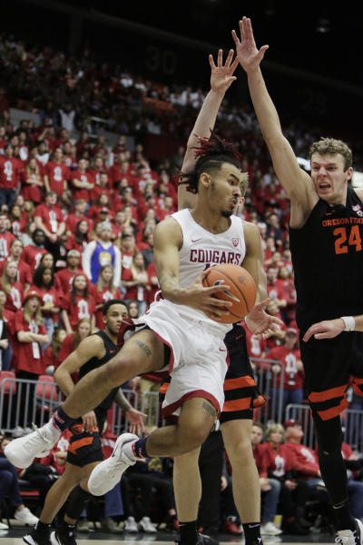 Washington State guard Isaac Bonton, left, passes the ball around Oregon State Oregon State guard Zach Reichle, back, and forward Kylor Kelley during the second half of an NCAA college basketball game in Pullman, Wash., Saturday, Jan. 18, 2020. Washington State won 89-76. (AP Photo/Young Kwak)
