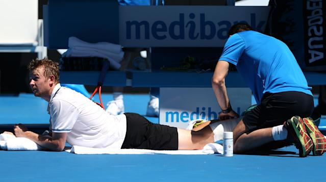 Andrey Golubev of Kazakhstan has his leg strapped by a trainer during his first round match against Stanislas Wawrinka of Switzerland at the Australian Open tennis championship in Melbourne, Australia, Monday, Jan. 13, 2014.(AP Photo/Rick Rycroft)
