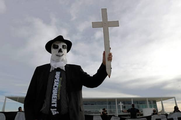 A demonstrator dressed as a ghost and wearing a tie calling for the impeachment of President Jair Bolsonaro holds a cross representing more than 300,000 COVID-19-related deaths outside the Planalto presidential palace in Brasilia, Brazil, Friday, March 26, 2021.