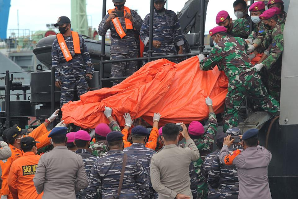 Officers lift a bag containing debris of the Sriwijaya Air plane which had just been unloaded from the Indonesian Navy ship.
