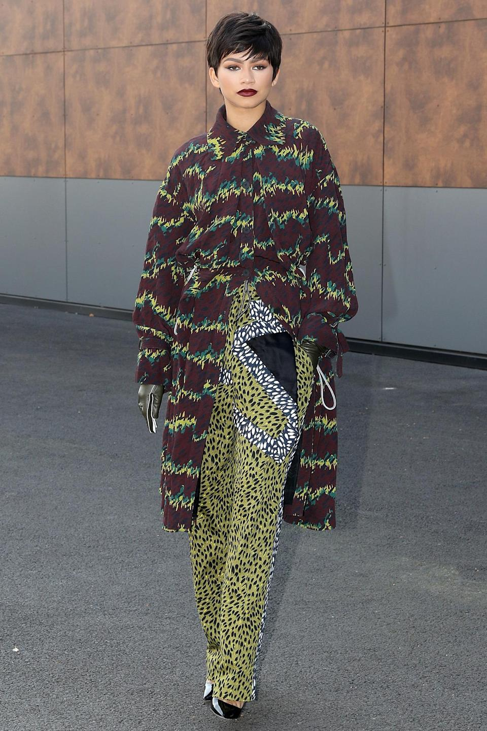 <p>At Kenzo, Carol Lim and Humberto Leon sent over-the-knee boot sandals, belt pochettes aka fannypacks, and clothes in graphic prints down the runway. Zendaya dressed appropriately in a green, brown, black, and white animal print ensemble from the brand's Fall 2015 collection. She wore a pixie wig and burgundy lipstick to match the outfit's coat. </p><p><i>Photo: Getty Images</i><br></p>