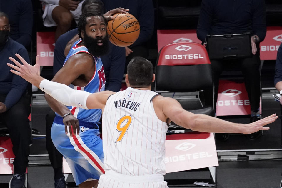 Orlando Magic center Nikola Vucevic, right, guards Brooklyn Nets guard James Harden, left, during the first half of an NBA basketball game, Saturday, Jan. 16, 2021, in New York. (AP Photo/Mary Altaffer)