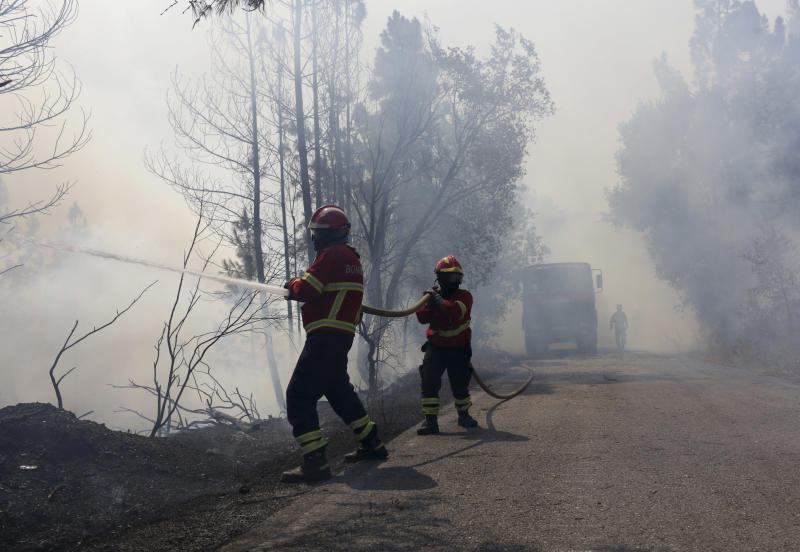 Firefighters battle a forest fire raging by the village of Lercas near Sardoal, central Portugal, Thursday, Aug. 17 2017. Portugal's government is taking the rare step of decreeing a state of public calamity ahead of a forecast rise in temperatures that authorities fear will worsen a spate of wildfires. (AP Photo/Armando Franca)