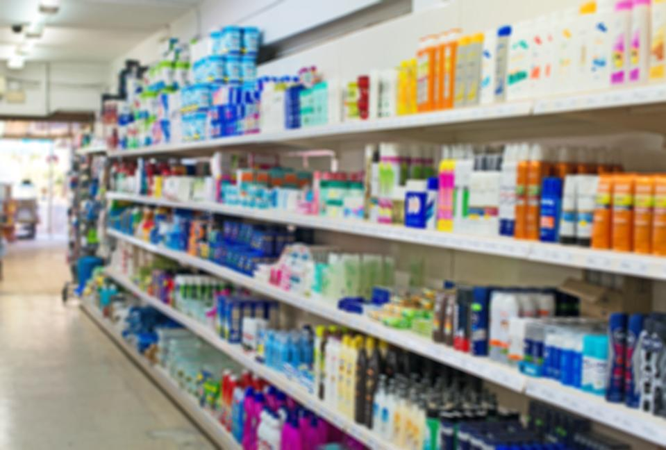 Blurred image of shelves with shampoos and household chemicals in supermarket.