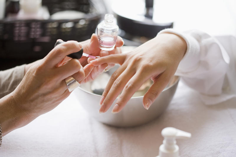 Pictured is a manicurist applying nail polish.