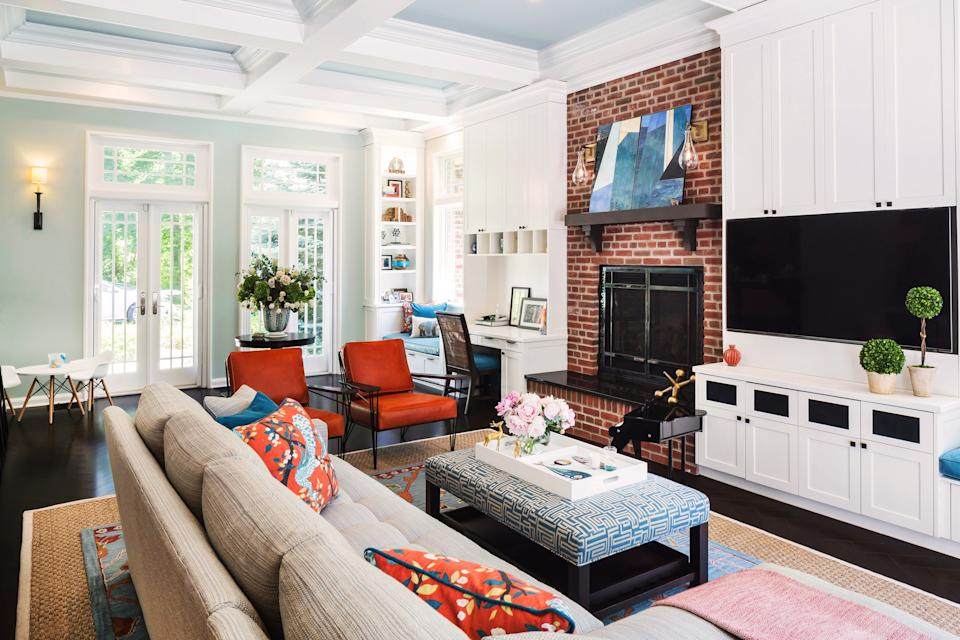 """<div class=""""caption""""> The family room is a colorful space for both the children and adults. McLeod lightened it up by painting the cabinets <a href=""""https://www.benjaminmoore.com/en-us"""" rel=""""nofollow noopener"""" target=""""_blank"""" data-ylk=""""slk:Benjamin Moore"""" class=""""link rapid-noclick-resp"""">Benjamin Moore</a>'s Simply White and the interiors of the ceiling coffers a blend of Simply White and Palladian Blue. Even more color was added with the addition of bright orange leather armchairs from <a href=""""https://www.olystudio.com/"""" rel=""""nofollow noopener"""" target=""""_blank"""" data-ylk=""""slk:Oly Studio"""" class=""""link rapid-noclick-resp"""">Oly Studio</a>, and coordinating throw pillows made with <a href=""""https://www.robertallendesign.com/fabric"""" rel=""""nofollow noopener"""" target=""""_blank"""" data-ylk=""""slk:Robert Allen"""" class=""""link rapid-noclick-resp"""">Robert Allen</a> fabric. The custom sofa is from <a href=""""https://www.theodorealexander.com/"""" rel=""""nofollow noopener"""" target=""""_blank"""" data-ylk=""""slk:Theodore Alexander"""" class=""""link rapid-noclick-resp"""">Theodore Alexander</a> with fabric from <a href=""""https://www.fabricut.com/stroheim"""" rel=""""nofollow noopener"""" target=""""_blank"""" data-ylk=""""slk:Stroheim"""" class=""""link rapid-noclick-resp"""">Stroheim</a> and paired with an ottoman table from <a href=""""https://www.arhaus.com/"""" rel=""""nofollow noopener"""" target=""""_blank"""" data-ylk=""""slk:Arhaus"""" class=""""link rapid-noclick-resp"""">Arhaus</a>. </div>"""