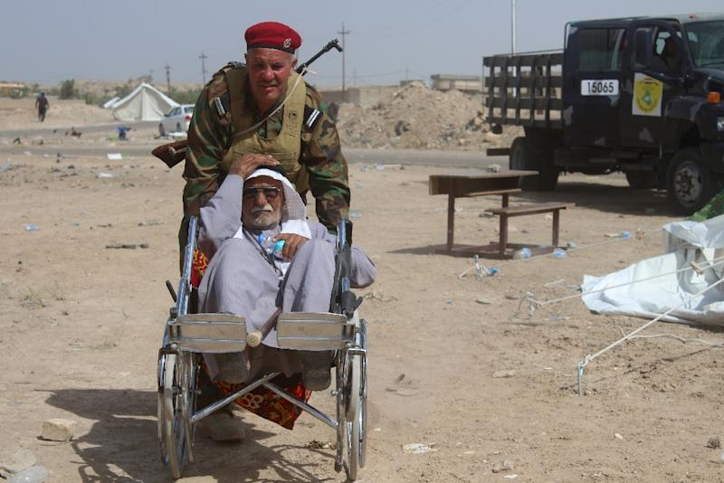 A displaced Iraqi man who was evacuated from his village is pushed in a wheelchair as he arrives at a safe zone in Subayat on June 12, 2016 (AFP Photo/Moadh al-Dulaimi)